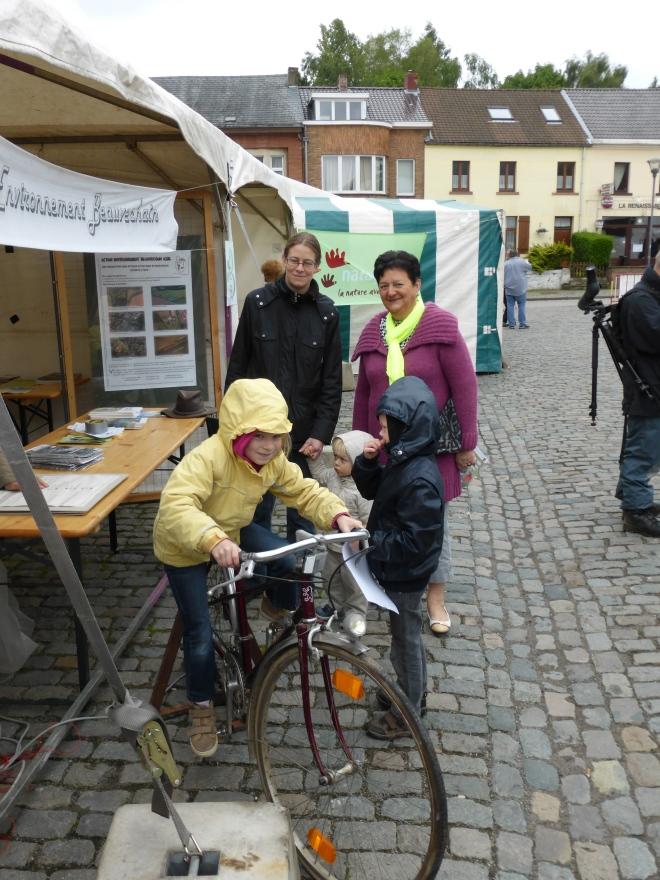 Devant le stand de AEB (Action Environnement Beauvechain), le vélo-quiz. Avec Marie-Josée Frix, conseillère communale.