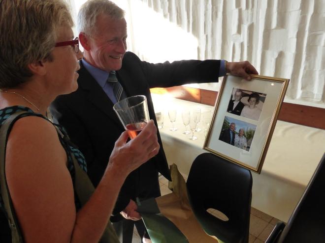 Raymond Evrard (échevin mais aussi jubilaire) montre fièrement les photos a Monique Lemaire-Noel (conseillère communale)